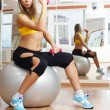 Girl posing with dumbbell in fitness gym on ball — Stock Photo #4339439