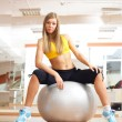 Stock Photo: blonde girl sittinig on silver ball in fitness gym