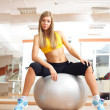 Blonde girl sittinig on silver ball in fitness gym — Stock Photo