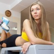 Girl sitting on steps in fitness gym — Stock Photo