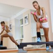Girl on step hold dumbbells in fitness gym — Stock Photo