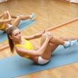 Stock Photo: Girl in shorts do exercise on floor mat in fitn