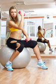 Girl posing with dumbbell in fitness gym on ball — Stock Photo