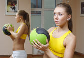 Girl with ball mirror background fitness gym — Stock Photo