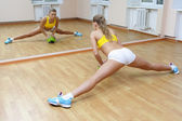Sports blonde girl do the splits in gym — Stock Photo