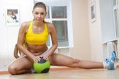 Sports blonde girl do the splits in gym — Stock Photo