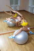 Girl in shorts do exercise on big ball in gym — Stock Photo