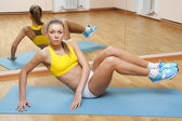 Girl in shorts do exercise on floor mat in gym — Stock Photo