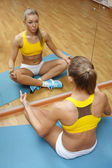 Girl sitting in yoga pose on floor mat in gym — Stock Photo