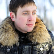 The young man, brooding eyes, a walk in the Winter Park - Stock Photo