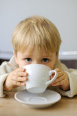 Little boy drinking from a cup tea in a cafe — Stock Photo
