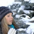 Nice girl looking at snow-covered fir branches — Stock Photo