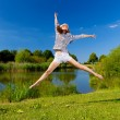 Stock Photo: Pretty young woman jumping