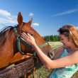 Horse and blond girl in paddock on summers - Stock Photo