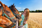 Horse and blond girl in paddock on summers — Stock Photo