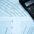 Diagrams and calculator — Stockfoto