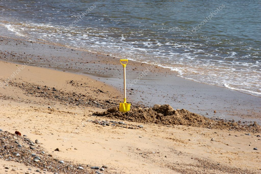 Childs Spade by the water edge on the beach  Stock Photo #4296592