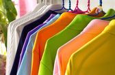 Colorful t-shirt on the hangers — Stock Photo