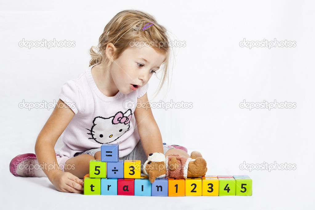 Happy little girl playing with colourful wooden blocks formed in train — Stock Photo #4047738