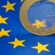 Euro coin on a european flag — Stock fotografie