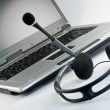Headset with laptop in the background - Stock Photo