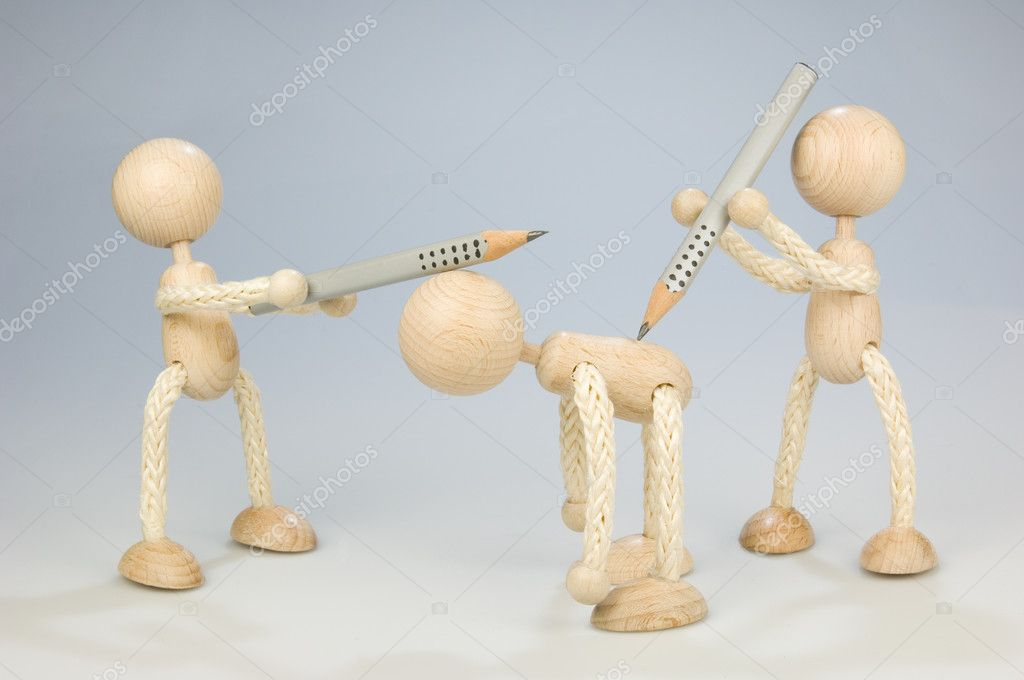 Bullying at work. Two wooden dolls attacks another one with pencils  Stock Photo #4024343