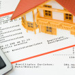 Model house on a bank account - Stock Photo