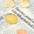 Euro-coins rolling over a newspaper — Stock Photo
