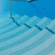 Steps and handrail into a swimming pool — Stock Photo #4048823