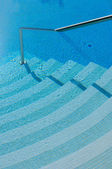 Steps and handrail into a swimming pool — Stock Photo