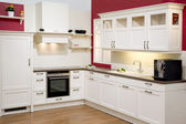 Modern fitted kitchen with red wall — Stock Photo