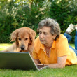 Senior woman with her dog at a laptop — Stock Photo