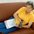 Senior woman with tv-remote control on a couch — Stock Photo #4062472