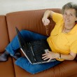 Senior woman with laptop on a couch — Stock Photo