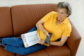 Senior woman with tv-remote control on a couch — Stock Photo