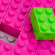 Green building block in a field of pink one — Stock Photo