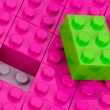 Green building block in field of pink one — Stock Photo #4076637