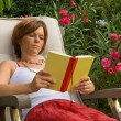 Reading woman in the garden — Stock Photo