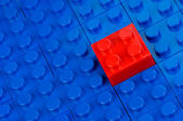Red building block in a field of blue one — Stock Photo