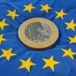 Euro coin on a european flag - Stock Photo