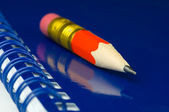 Short pencil on a blue notepad — Stock Photo