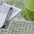 Peacounters wokplace with peas, pea tin and notepad — Stock Photo