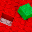 Stock Photo: Green building block in field of red ones