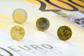 Euro-coins rolling over a 200-euro-banknote — Stock Photo