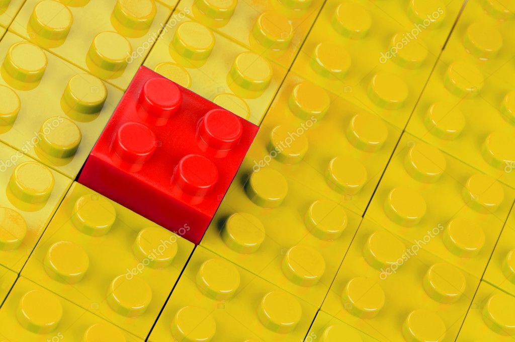 Red building block in a field of yellow ones — Stock Photo #4136053