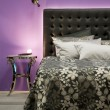 Bed in front of a purple wall — Stock Photo