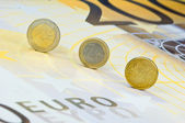 Euro coins rolling over a euro banknote — Stock Photo