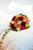 Bridal bouquet on a bed — Stock Photo