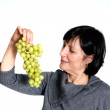 Aged woman with grapes — Stock Photo
