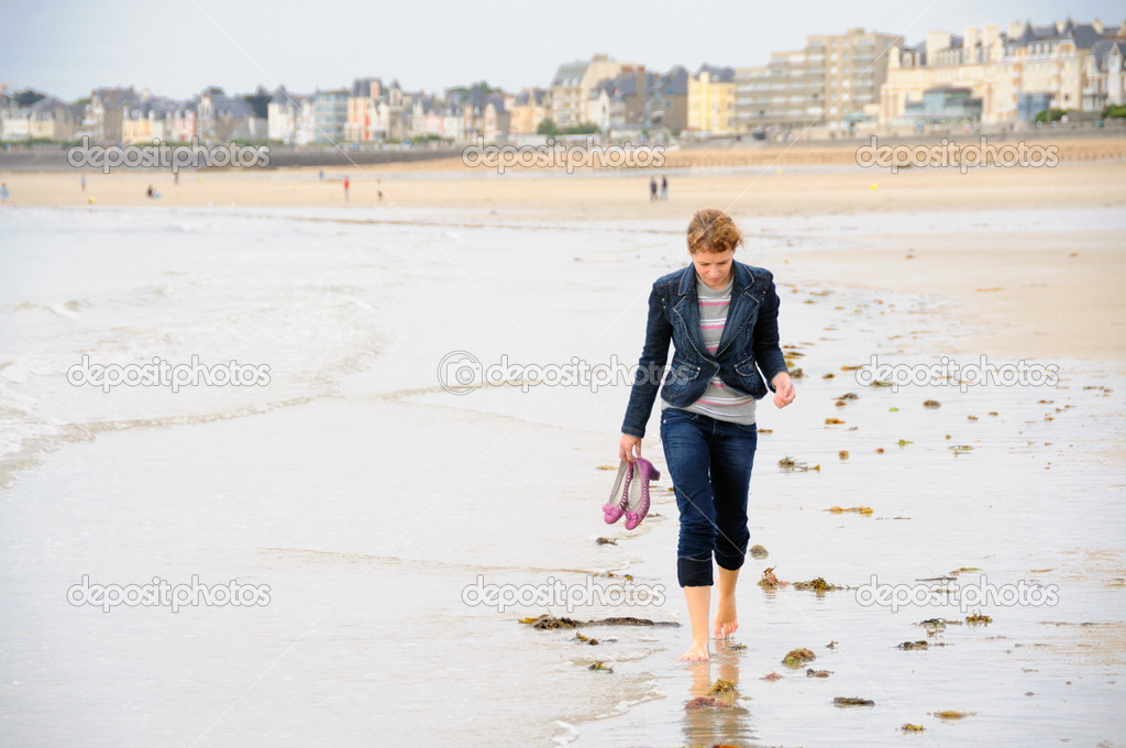Young woman walking barefoot on french beach — Stock Photo #4500019